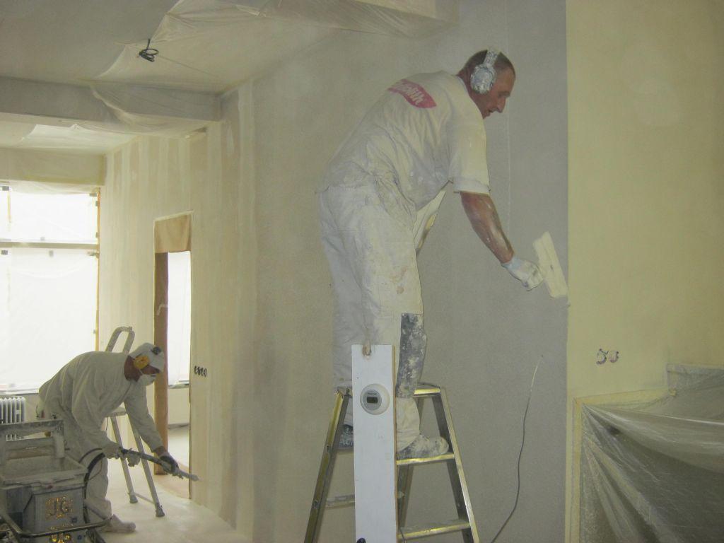 Stukadoors op de muur aan het stucen en spuiten